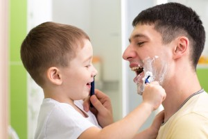 preschooler child attempting to shave his dad